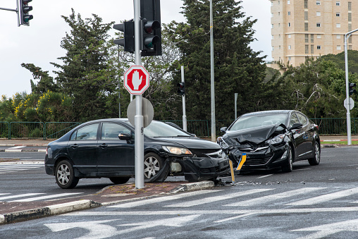 A crash at an intersection involving two cars that have been badly damaged