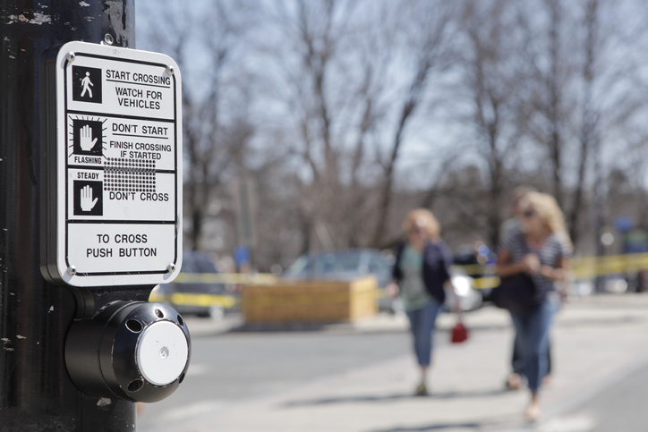 Close-up of crosswalk signage and button